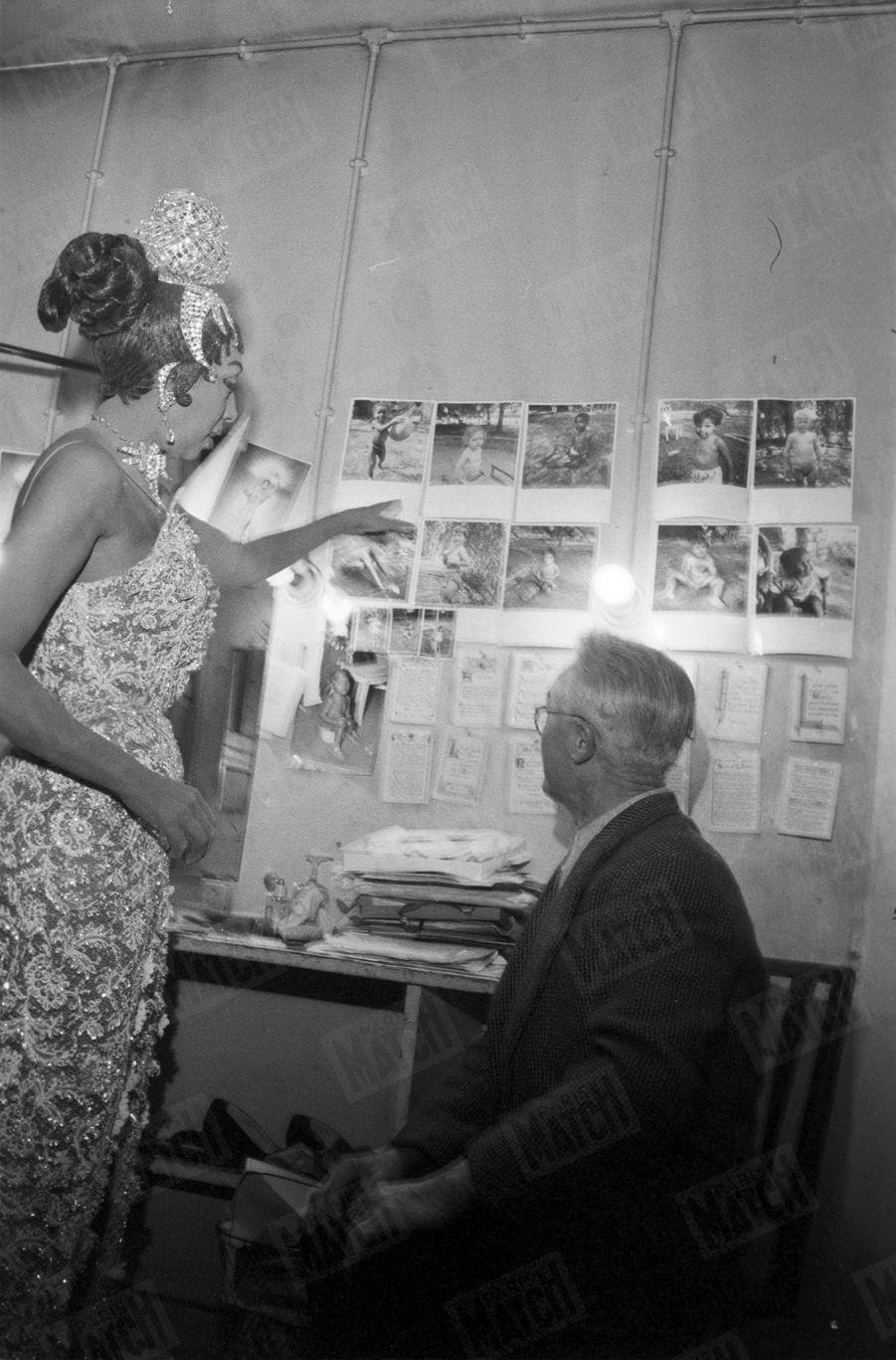 Joséphine Baker dans sa loge del'Olympia avec « Pépère », le chiffonnier de Saint Ouen qui avait retrouvé dans une poubelle le bébé adopté par la chanteuse en décembre 1959. La chanteuse montre les photos de sa tribu «arc-en-ciel».