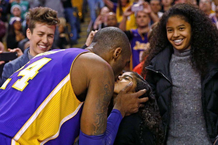 Kobe Bryant embrasse sa fille Gianna devant sa fille Natalia après un match en décembre 2015