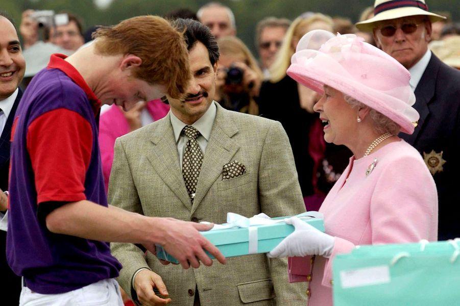 La Queen offre un cadeau à son petit-fils Harry lors d'un match de polo à Windsor en 2003.