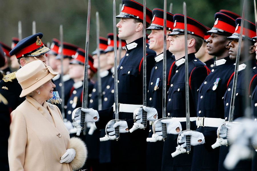 La reine Elizabeth II sourit à Harry alors qu'elle procède à son inspection des soldats britanniques dans le Surrey, en 2006.
