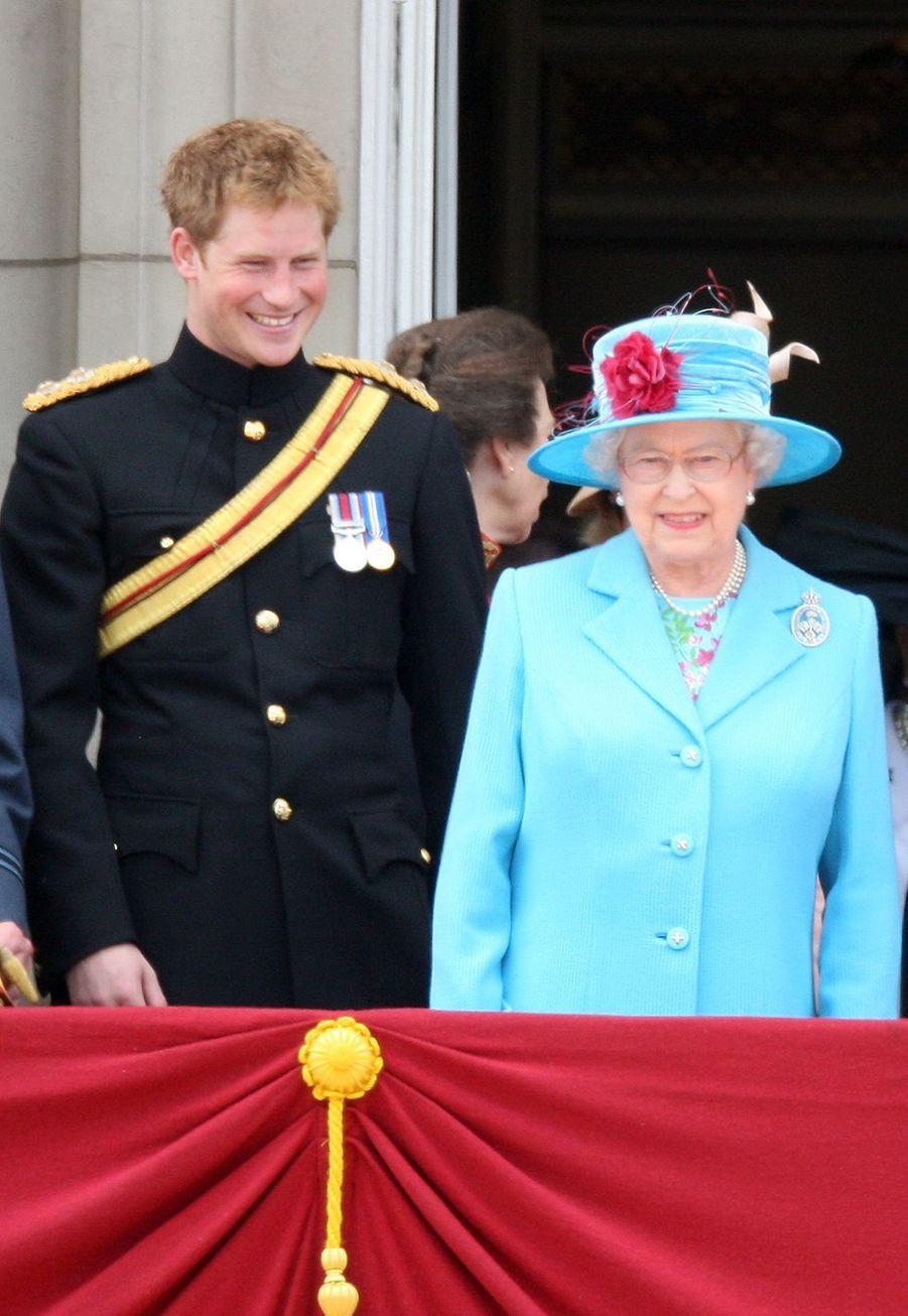 Harry partage des rires avec la Queen alors qu'ils se tiennent sur le balcon de Buckingham Palace en 2009.