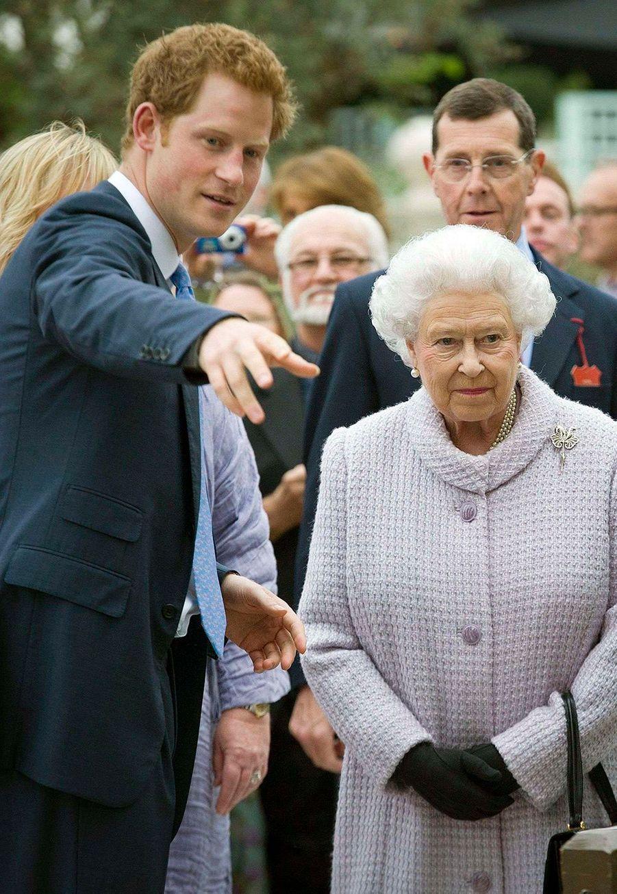 Harry fait visiter à la Queen le jardin de son ONG Sentebale à Londres en 2013.