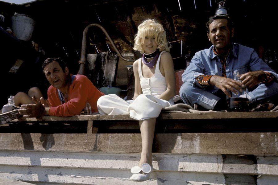 """Mireille Darc sur le tournage de """"Fantasia chez les ploucs"""" avec Lino Ventura et Jean Yanne."""