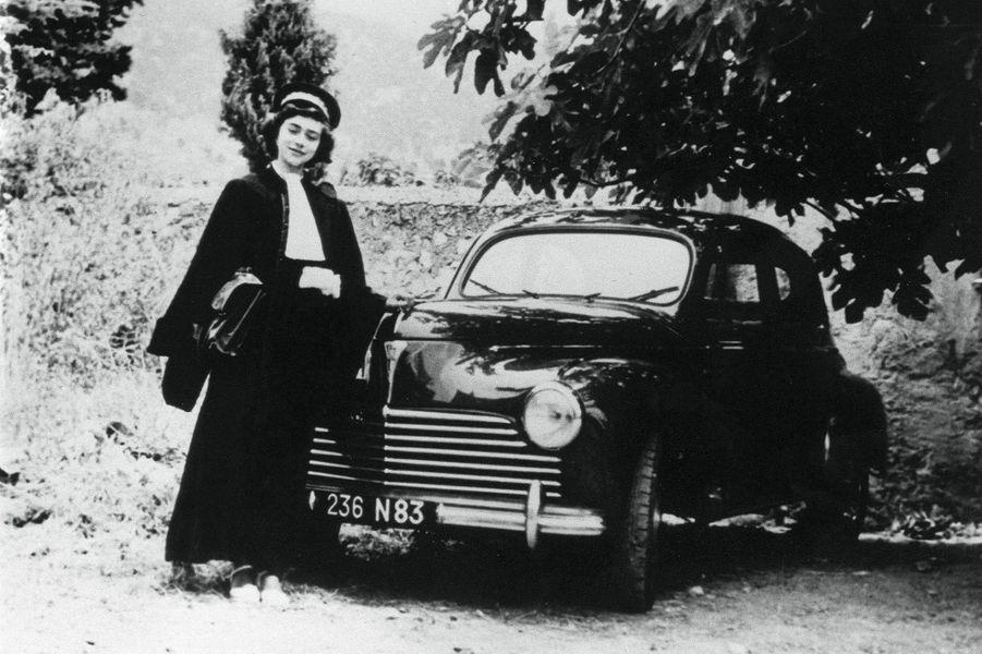 Mireille Darc pose près d'une Peugeot 203.