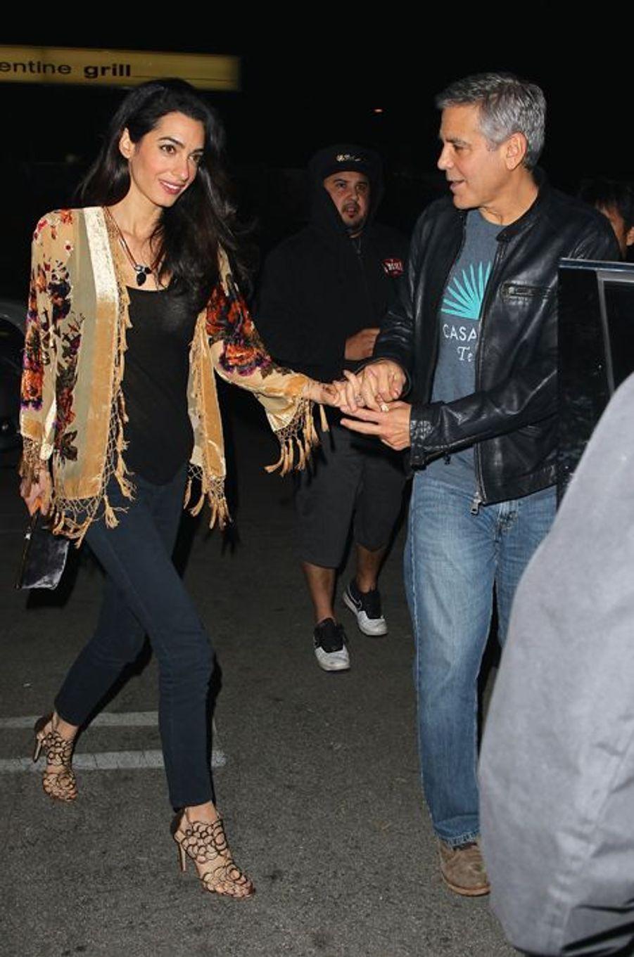 Accompagnée de son époux pour une sortie en tête-à-tête, Amal Clooney avait opté pour une tenue originale mais très osée : habillée d'une veste à franges de la griffe Shantique (160 euros), d'un collier Akong London (395 euros), d'une paire de sandales Oscar de la Renta (835 euros) et d'une pochette Dolce & Gabbana (1.230 euros), la spécialiste du droit international portait un look à 2.620 euros.