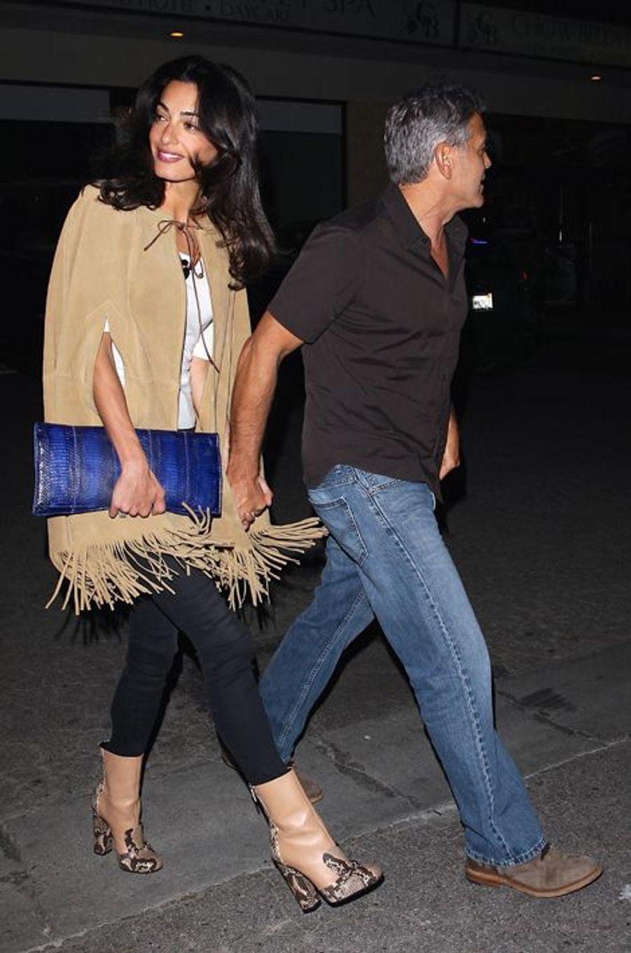 Avec son mari pour une sortie entre amis, Amal Clooney avait revêtu une cape Yves Saint Laurent (3.070 euros), une paire de bottines Gucci (1.495 euros) et un collier Akong London (445 euros). Prix total de la tenue : 5.010 euros.