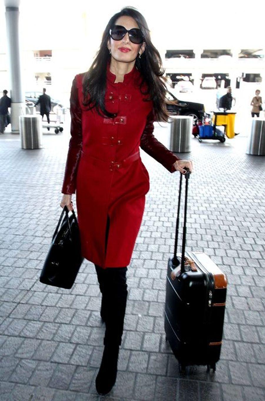 De nouveau à l'aéroport en direction de l'Angleterre, Amal Clooney avait misé sur un long manteau rouge de la maison Versace (1.870 euros), une paire de bottes Prada (895 euros) et un sac Dior (4.450 euros). Un look pour une valeur totale de 7.215 euros.
