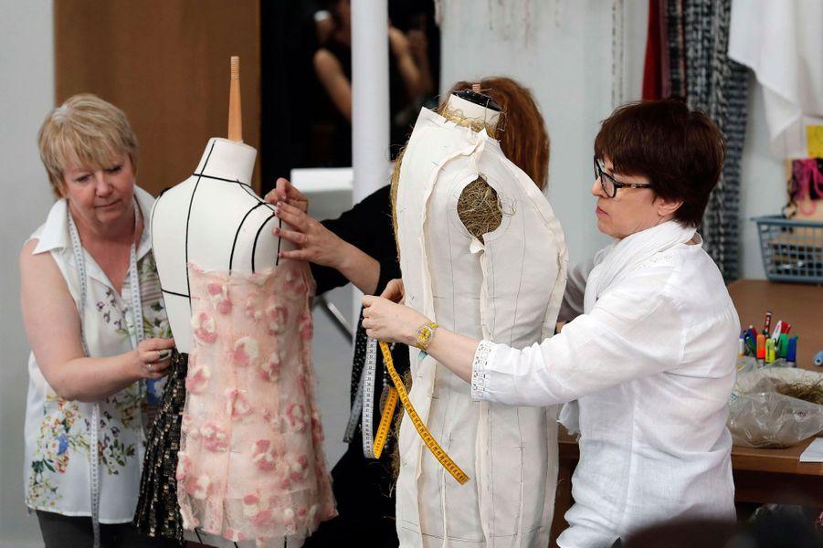 Les premières d'atelier s'affairent derrière les mannequins.