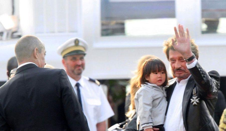 Johnny Hallyday tient dans ses bras la petite Joy, l'une de ses deux filles adoptives.
