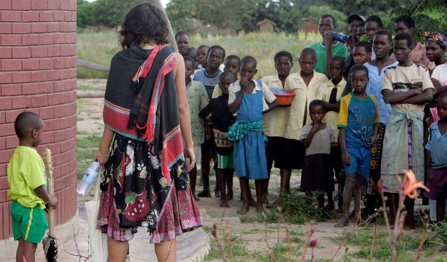 Son fils David regardant les enfants de l'école de Namite, que sa mère finance.
