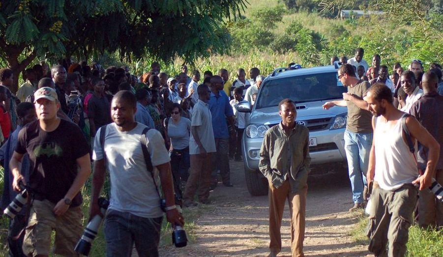 Une foule de passants et de journalistes se sont amassés autour de la voiture transportant La Madonne et ses enfants.