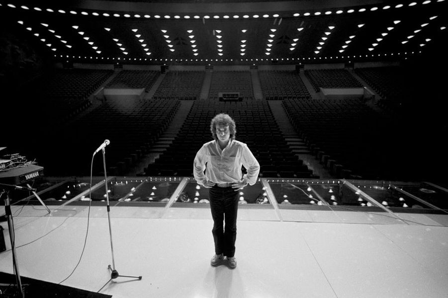 A Paris, pendant une répétition sur la scène du Palais des Congrès, Michel Sardou, debout, dos à la salle vide, novembre 1978