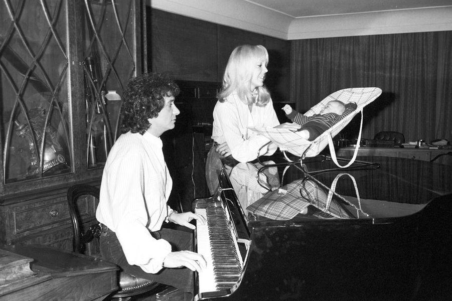 Chez lui, Michel Sardou joue du piano, en compagnie de son épouse Babette et de son fils Davy, novembre 1978