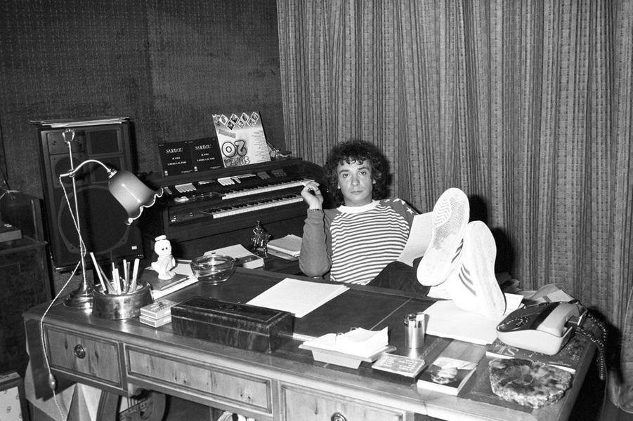 Michel Sardou, chez lui, assis, les pieds sur son bureau, relisant un texte, une cigarette entre les doigts
