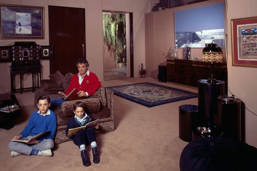 Michel Sardou dans le salon de son hôtel particulier du XVIe arrondissement de Paris, avec ses fils Romain, 13 ans, et Davy, 8 ans, le 11 janvier 1...