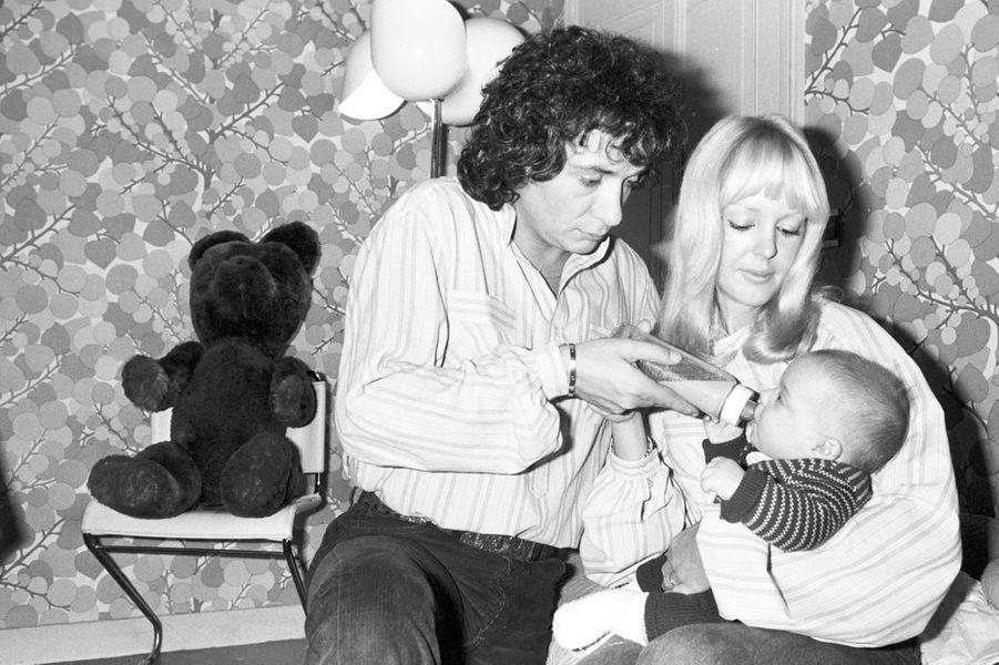 Michel Sardou et son épouse donnent le biberon à leur fils Davy, 1978