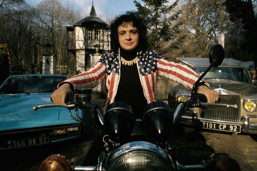 Michel Sardou sur sa moto, devant sa maison, mars 1974