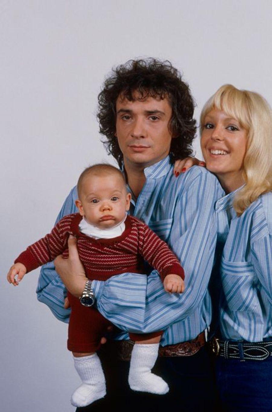 Michel Sardou tient dans ses bras son fils Davy, 5 mois, au côté de son épouse Babette