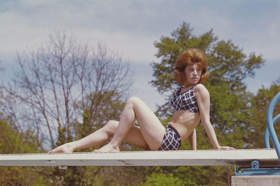 1961 : assise sur le plongeoir d'une piscine construite au-dessus d'une petite rivière, près de sa maison de Brunoy