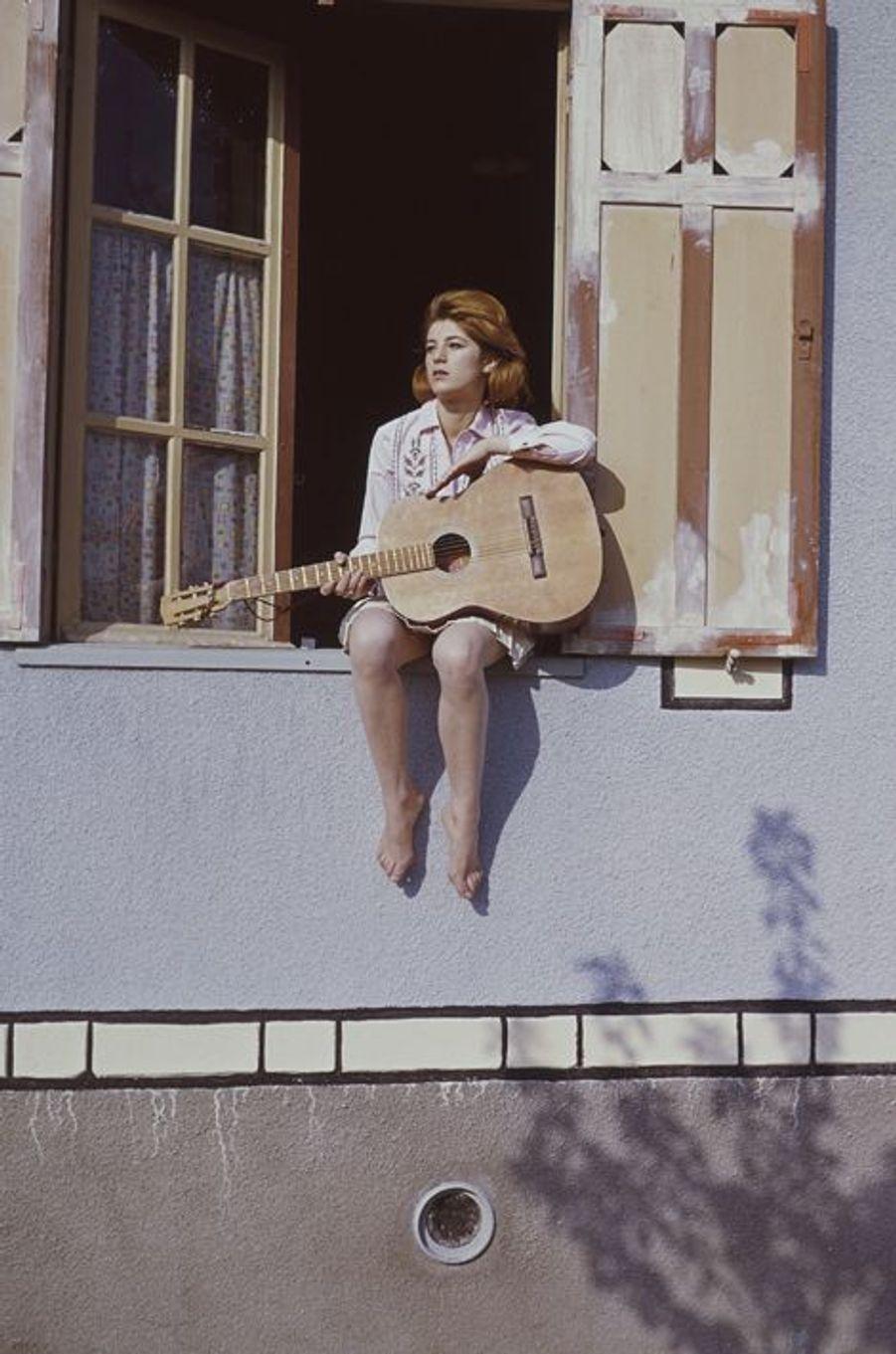 Assise sur le rebord de la fenêtre de sa maison de Brunoy, une guitare dans les bras. La chanteuse a 16 ans