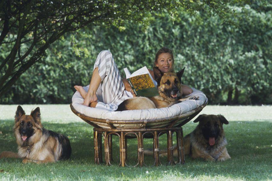 Dans sa maison de Feucherolles, à l'ombre d'un arbre aux côtés de ses trois chiens, Plouc, Houps et Fine. Ici en 1993
