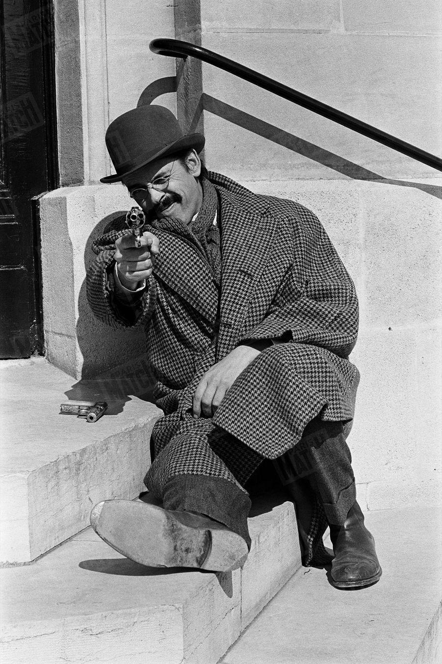 """Jacques Brel sur le tournage du film """"La Bande à Bonnot"""" d'Edouard Molinaro, place de l'Opéra à Paris, en avril 1968."""