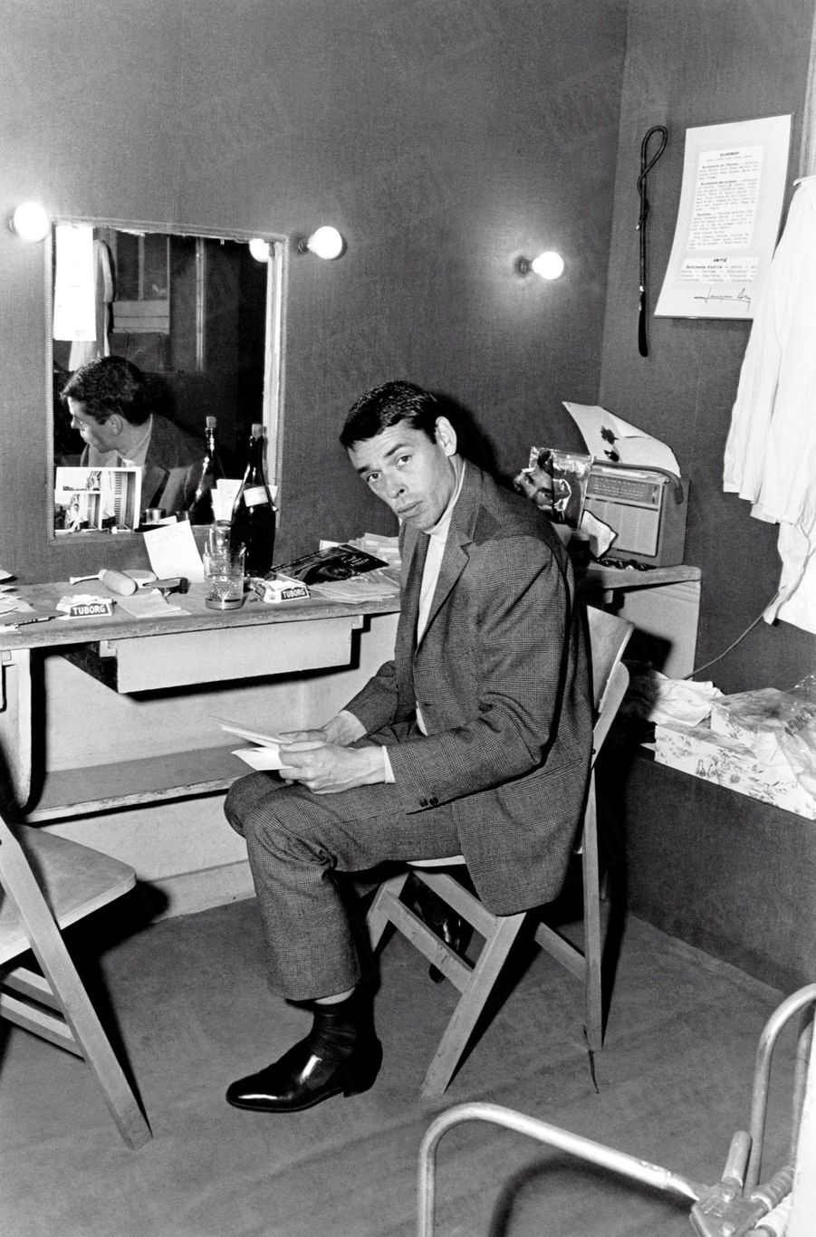 Jacques Brel lisant un télégramme dans sa loge, le 19 octobre 1964