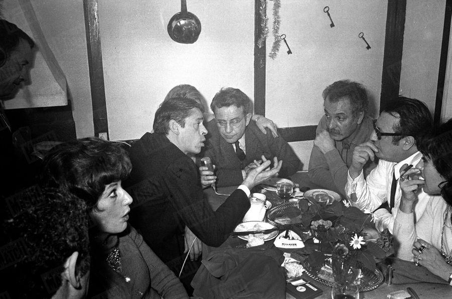 Jacques Brel, lors du 30e anniversaire du Théâtre des Trois Baudets, à Pigalle, le 18 décembre 1967. Attablés de gauche à droite : Yves Robert de dos, Rosy Varte, Jacques Brel parlant au micro, face à Jacques Canetti, Georges Brassens et Raymond Devos.