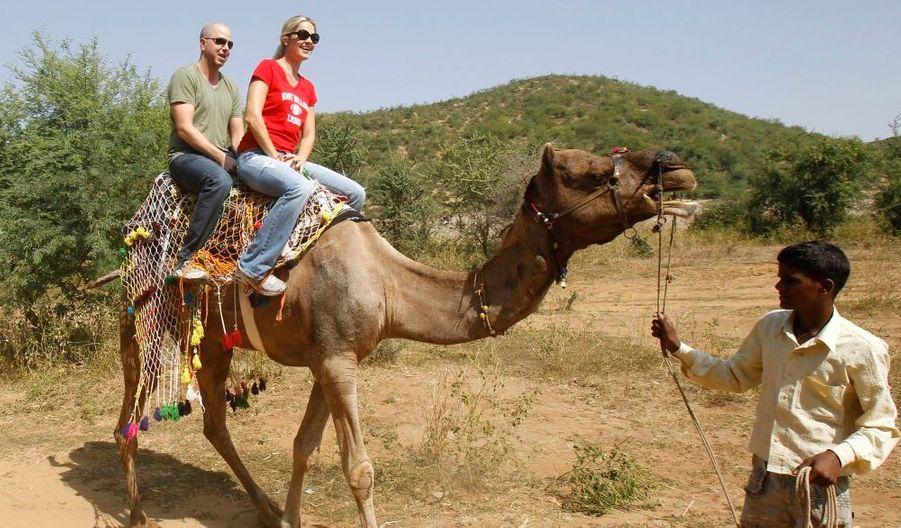 Des invités non-identifiés participants à la balade à dos de chameau dans le parc national