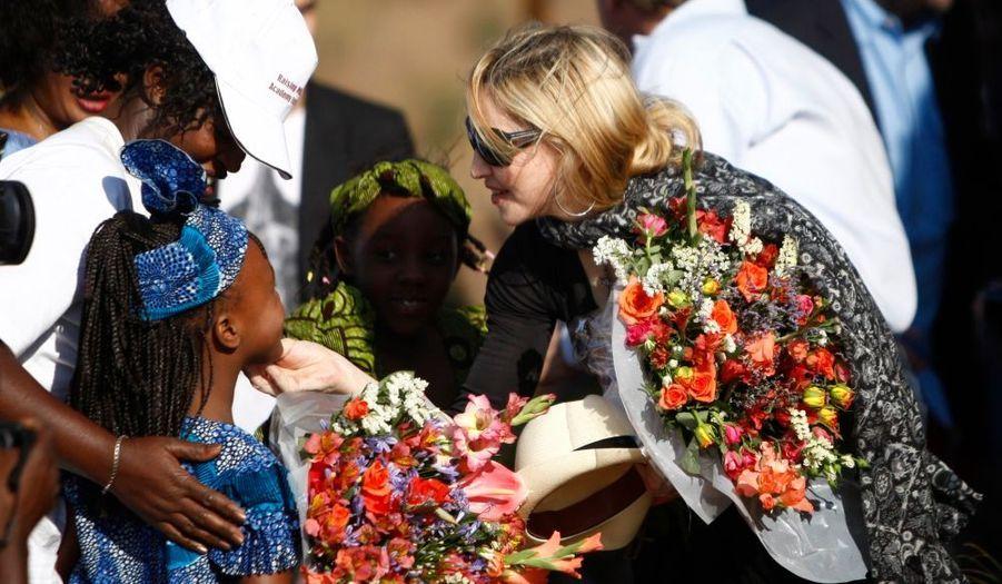 Une petite Malawite offre des fleurs à Madonna, qui finance la construction d'une école pour filles dans le village de Chinkhota, à une quinzaine de kilomètres de la capitale, Lilongwe. L'établissement scolaire devrait ouvrir dans deux ans et accueillir 500 élèves du primaire, pour un coût de 15 millions de dollars.