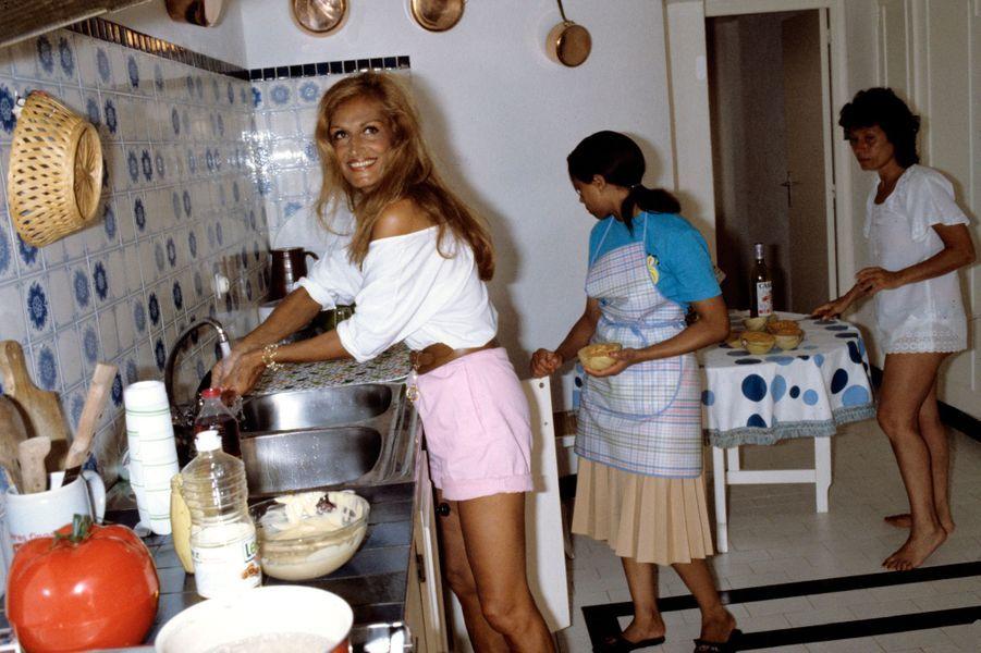 Dalida souriante, entourée de sa cousine Rosy et de sa femme de chambre, s'affaire dans la cuisine de sa villa de Porto-Vecchio en Corse, Août 1982