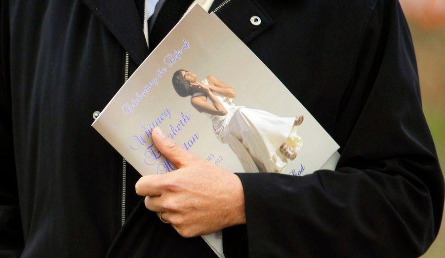 Le programme de la cérémonie, dans la main d'un proche.
