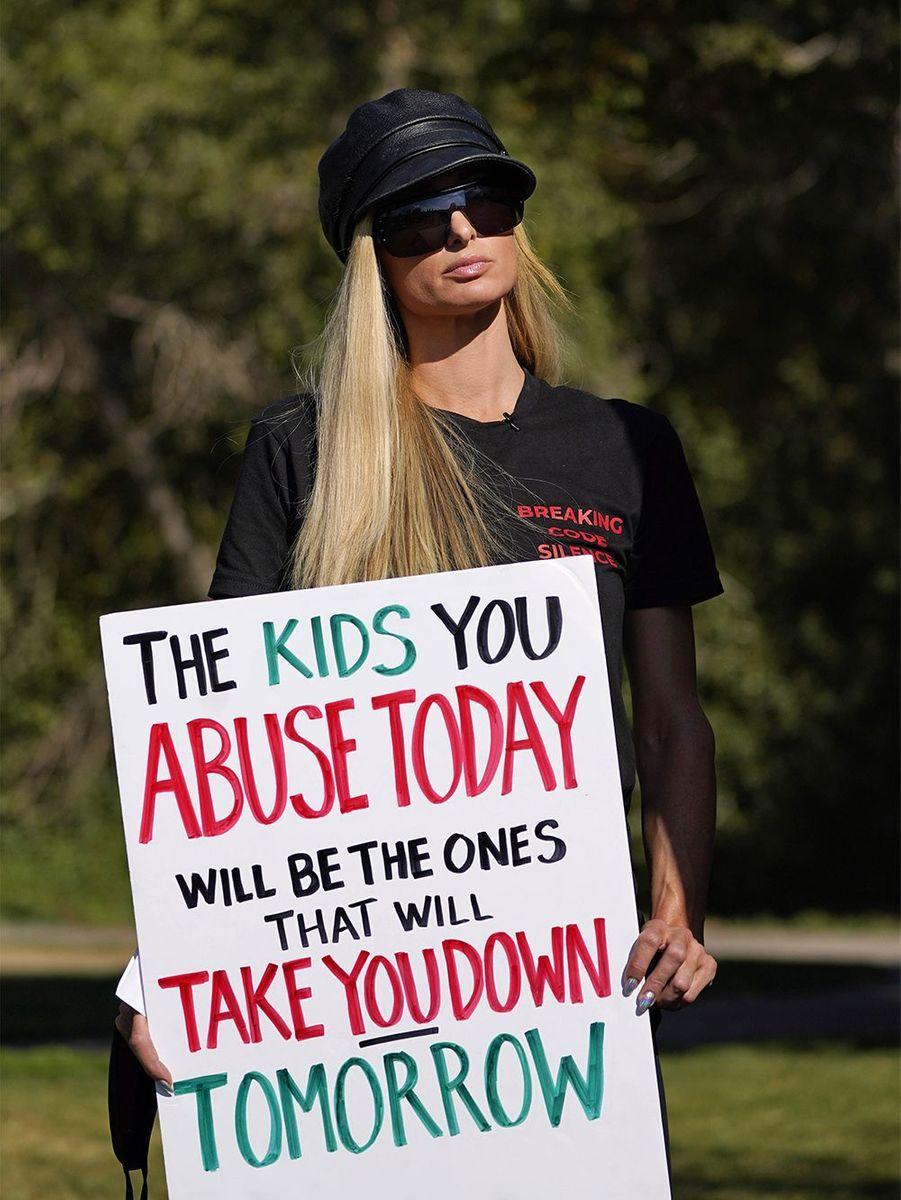 Paris Hilton a manifesté vendredi afin de demander la fermeture de l'école privée où elle avait été placée alors qu'elle était encore adolescente.