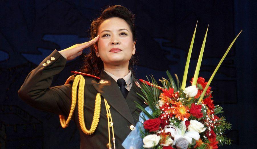 La soprano chinoise, engagée à 18 ans dans les rangs de l'armée comme simple soldat, s'est rapidement imposée en chanteuse vedette de l'Armée populaire de libération. Elle a aujourd'hui le grade de générale de division.