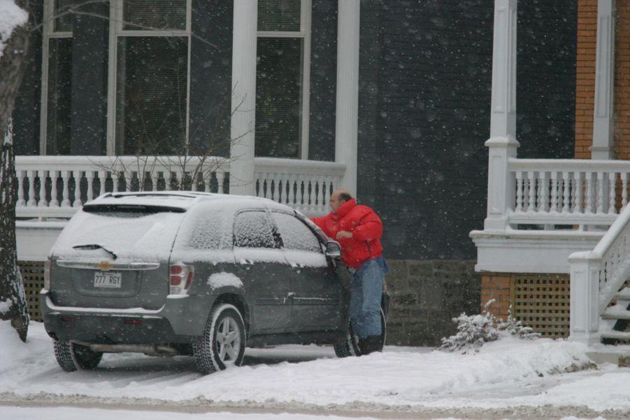 A Montréal, en décembre 2005, après sa condamnation. Alain Juppé dégivre le pare-brise de sa voiture