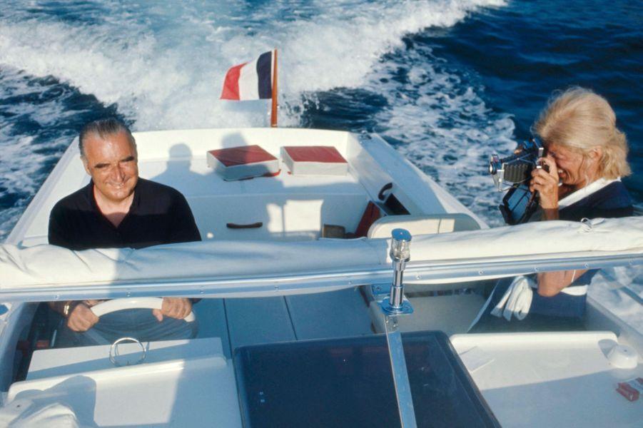 """Alors que François Hollande a annoncé qu'il ne prendrait qu'une semaine officielle de vacances du 12 au 19 août prochain, retour en images sur nos présidents de la République loin de l'Elysée.Georges Pompidou aux commandes d'un bateau """"Arcoa"""" avec son épouse Claude le photograhiant lors de leurs vacances à Brégançon."""