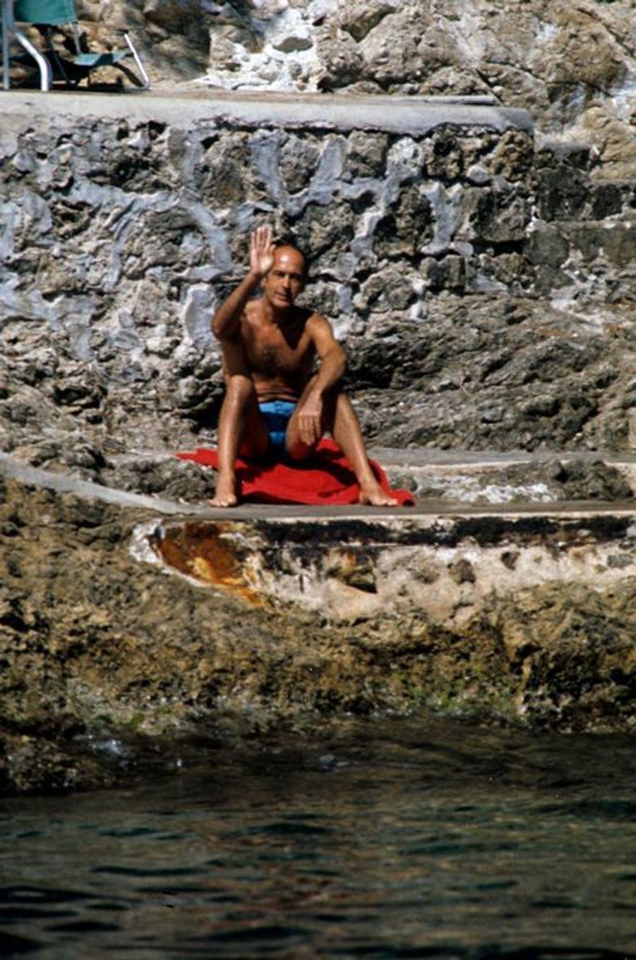 Valéry Giscard d'Estaing bronzé, en maillot de bain, assis en bord de mer, saluant de la main le photographe, en vacances chez des amis à la Villa Primavera au Cap Ferrat.