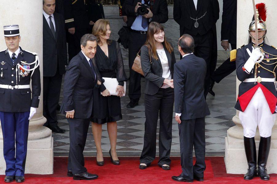 Après avoir été battu par François Hollande, Nicolas Sarkozy quitte l'Elysée. Sur le perron, les premières dames se croisent : Valérie Trierweiler et Carla Bruni-Sarkozy.