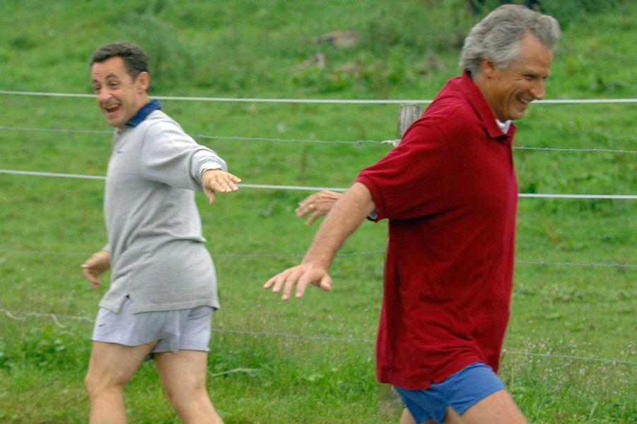 Septembre 2005, à Evian, lors des journées parlementaires de l'UMP : Nicolas Sarkozy, ministre de l'Intérieur, croise Dominique de Villepin, son rival, lors d'un jogging. Pour la photo, les deux hommes décrochent de grands sourires.
