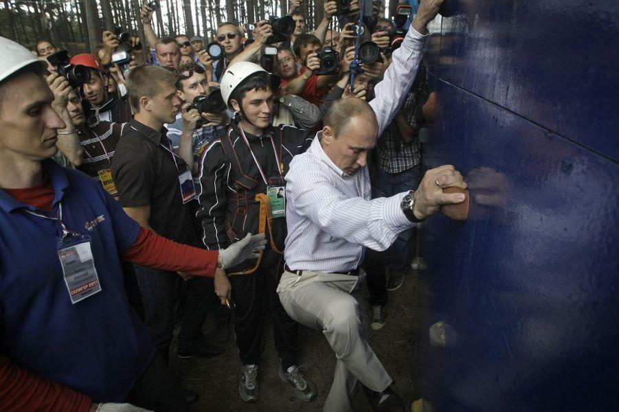 Vladimir Poutine escalade un mur au bord du lac Seliger, en août 2011