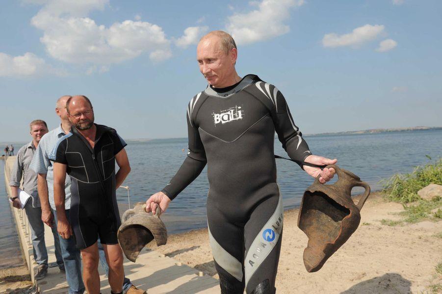 Vladimir Poutine remonte des objets pêchés sur un site archéologique de Taman, en août 2011
