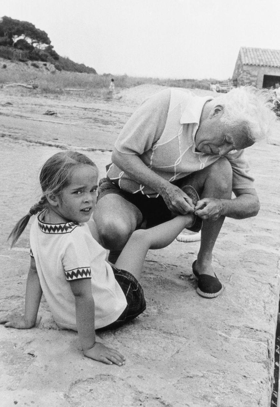 En vacances dans le Lavandou, Charlie Chaplin (1889-1977), 67 ans, aide sa fille Victoria à remettre sa sandale.