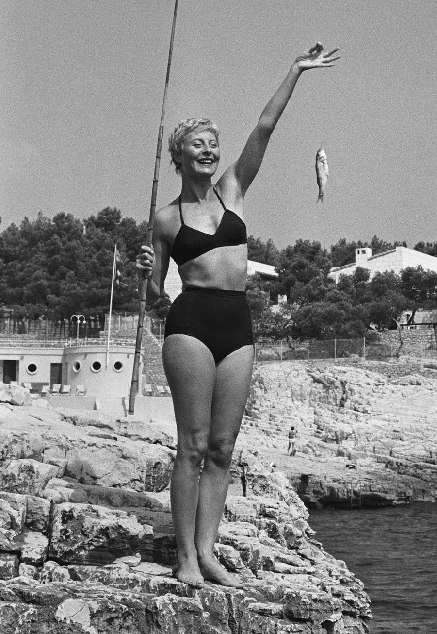 Michèle Morgan (1920-2016) s'essaie avec succès à la pêche à la ligne.
