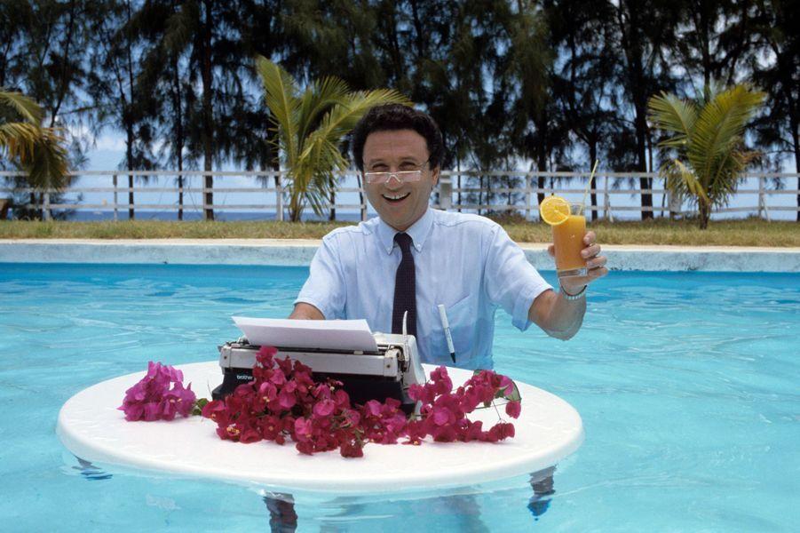 La Réunion, 1987 : Michel Drucker devant sa machine à écrire dans une charmante piscine.