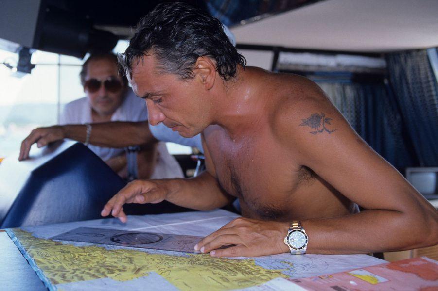 Monte-Carlo, août 1984 : le chanteur Michel Sardou, torse nu, étudie une carte à bord de son bateau.