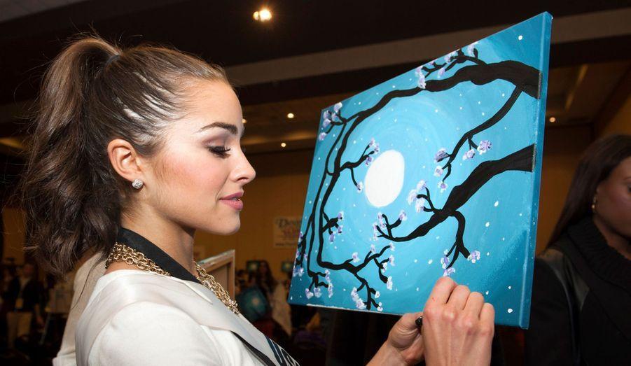Début décembre, Olivia signe une toile pour une oeuvre caritative