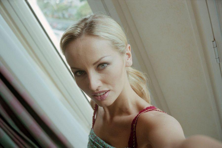 Le 52ème Festival de Cannes se déroule du 12 au 23 mai 1999 : attitude souriante d'Adriana KAREMBEU se prenant en photo.