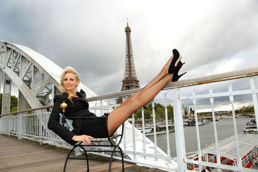 Le top model Adriana KAREMBEU pose devant la tour Eiffel sur la passerelle Debilly. Elle est assise sur un fauteuil Patrick Goavec.
