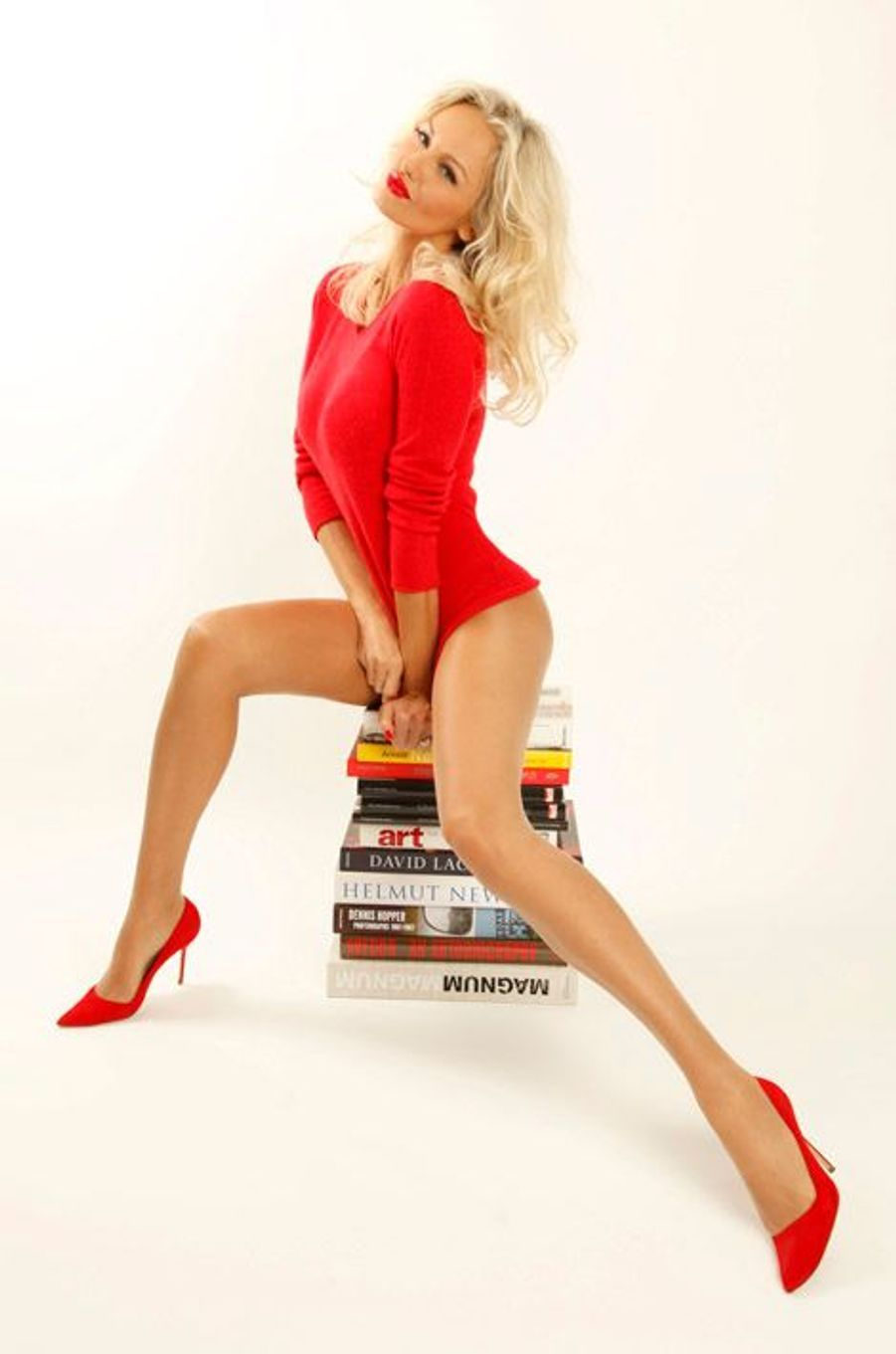 Le top model Adriana KAREMBEU joue les pin-up fifties, assise sur des livres de photos et d'art. Photo studio.