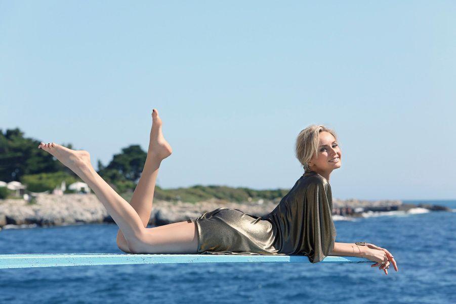 Attitude souriante d'Adriana KAREMBEU allongée sur le plongeoir surplombant la mer à l'hôtel du Cap-Eden-Roc.